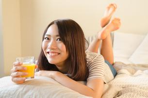 オレンジジュースを持って笑っている女性 FYI01078273