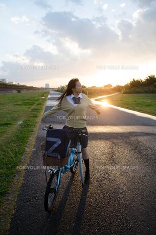 自転車にまたがって深呼吸する女子学生 FYI01078284