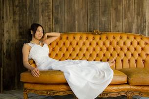 大きなソファに座るドレス姿の女性 FYI01078309