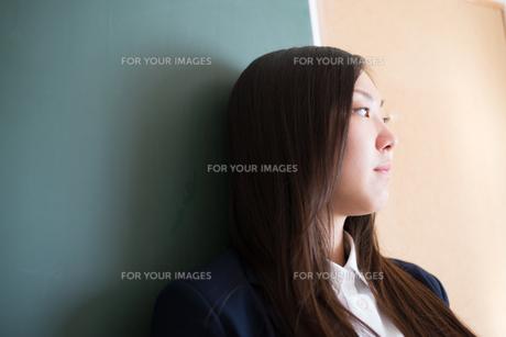 黒板の前で横を向いている女子高校生 FYI01078347