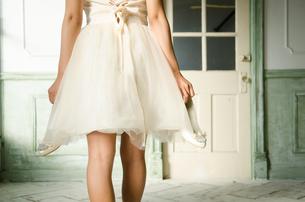 靴を脱いだドレス姿の女性の後ろ姿 FYI01078377