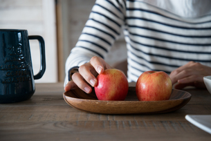 ふたつのりんごを触っている女性の手元 FYI01078378