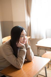 机で頬杖をついている女子高校生 FYI01078388