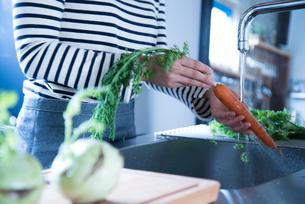 キッチンで野菜を洗っている女性の手元 FYI01078391