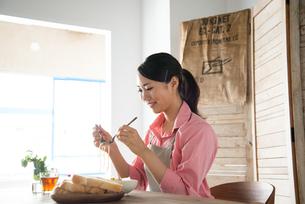 エプロンをしてパスタを食べようとしている女性 FYI01078398