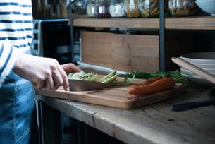 キッチンで野菜を切っている女性 FYI01078405