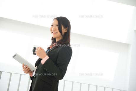 タブレットとコーヒーを持って笑っている女性 FYI01078413