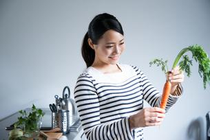 キッチンでにんじんを持っている女性の素材 [FYI01078422]