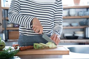 キッチンで野菜を切っている女性の手元 FYI01078423