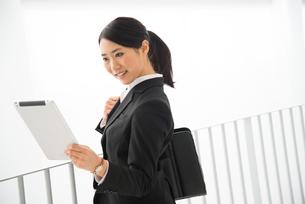 タブレットを見ているスーツ姿の女性 FYI01078427