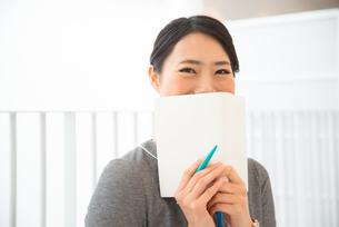 スケジュール帳を持って笑っている女性 FYI01078432