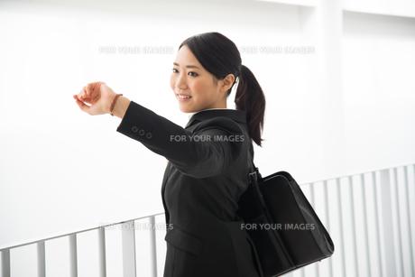 時計を見ているスーツ姿の女性 FYI01078437