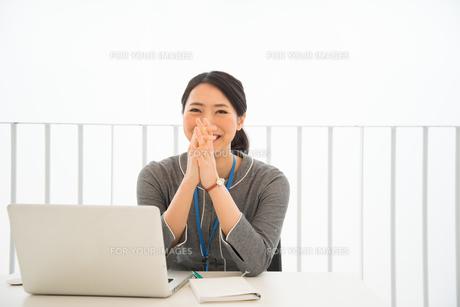 ノートパソコンの前で笑っている女性 FYI01078443