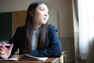 机に座って窓の外を眺めている女子高校生 FYI01078449