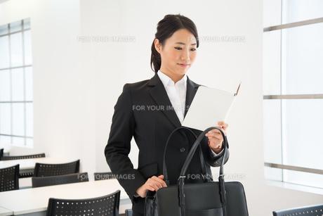 スケジュール帳を見ているスーツ姿の女性の素材 [FYI01078450]
