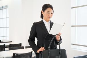 スケジュール帳を見ているスーツ姿の女性 FYI01078450