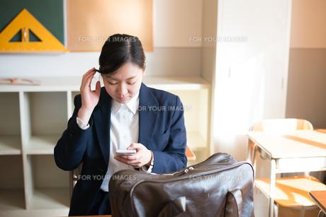 教室で携帯電話をいじっている女子高校生 FYI01078451
