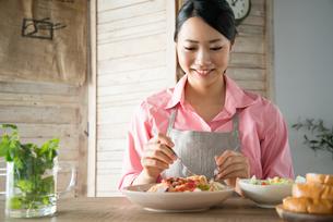 エプロンをしてパスタを食べようとしている女性 FYI01078452
