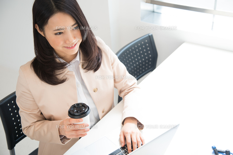 コーヒーを片手にパソコンを触っている女性 FYI01078456
