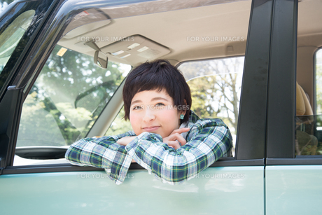 車から乗り出して笑う女性の素材 [FYI01078475]