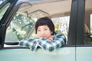 車から乗り出して笑う女性 FYI01078475