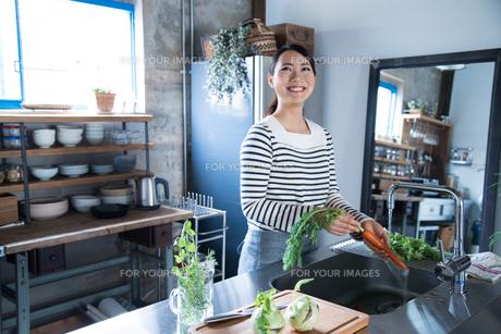 キッチンで野菜を洗っている女性 FYI01078477
