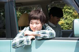 車から乗り出して笑う女性 FYI01078481