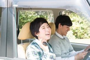 車の鍵を持って笑う女性と笑う男性 FYI01078490