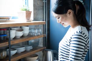 キッチンで横を向いている女性 FYI01078491