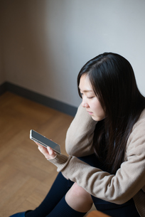座って携帯電話を触っている女子高校生 FYI01078492