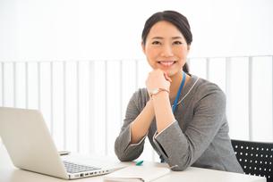 パソコンの前で笑っている女性 FYI01078493