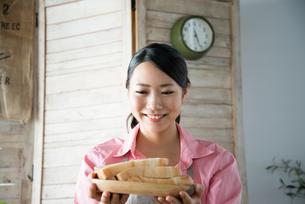 食パンを持って笑っている女性 FYI01078494