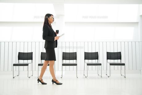 タブレットとコーヒーを持って歩いている女性 FYI01078500