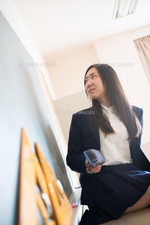黒板の前で黒板消しを持っている女子高校生 FYI01078501