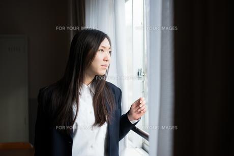 窓の外を眺めている女子高校生 FYI01078506