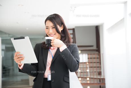 タブレットとコーヒーを持っている女性 FYI01078508