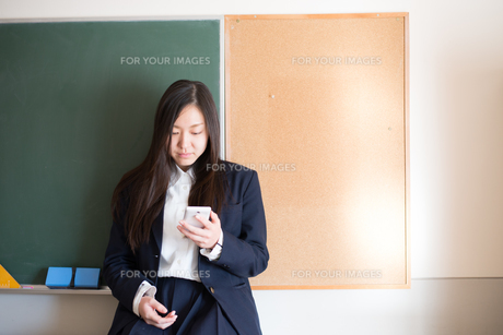 黒板の前で携帯をいじっている女子高校生 FYI01078517