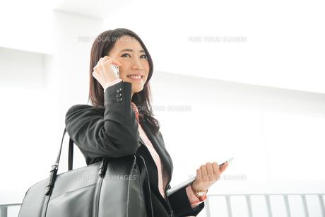 タブレットを持って電話をしている女性 FYI01078521