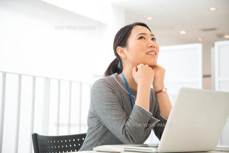 ノートパソコンの前で頬杖をついている女性 FYI01078531