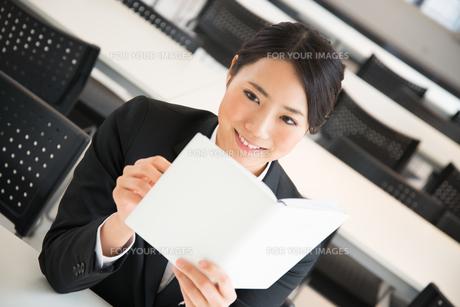 スケジュール帳を見ているスーツ姿の女性 FYI01078533