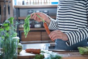 キッチンでにんじんを持っている女性の手元 FYI01078538