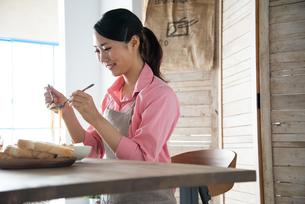 エプロンをしてパスタを食べようとしている女性 FYI01078544