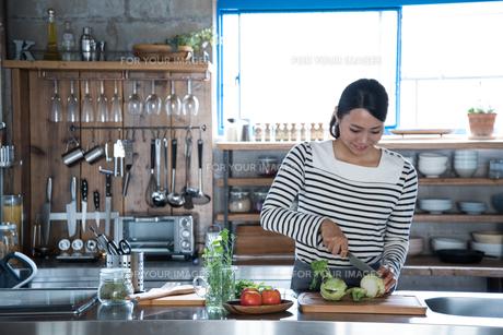 キッチンで野菜を切っている女性 FYI01078555
