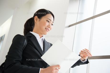 スケジュール帳を持って時計を見ているスーツ姿の女性 FYI01078561