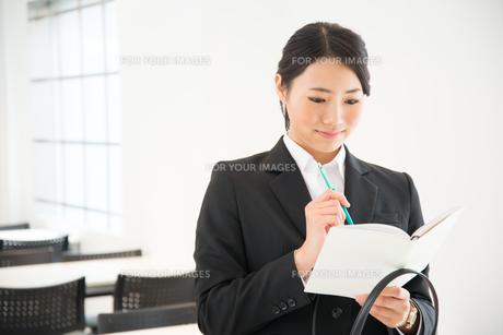 スケジュール帳を見ているスーツ姿の女性 FYI01078575