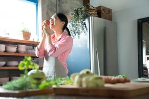 キッチンでりんごを食べようとしている女性 FYI01078582