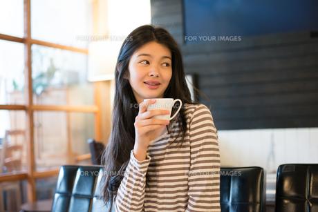 カフェでカップを持っている女性 FYI01078584