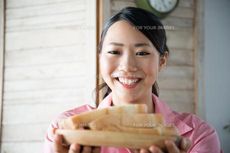 食パンを持って笑っている女性 FYI01078590