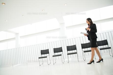 タブレットとコーヒーを持って歩いている女性 FYI01078602