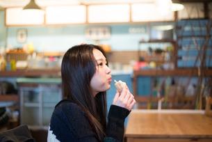 カフェでサンドイッチを食べている女性の素材 [FYI01078603]